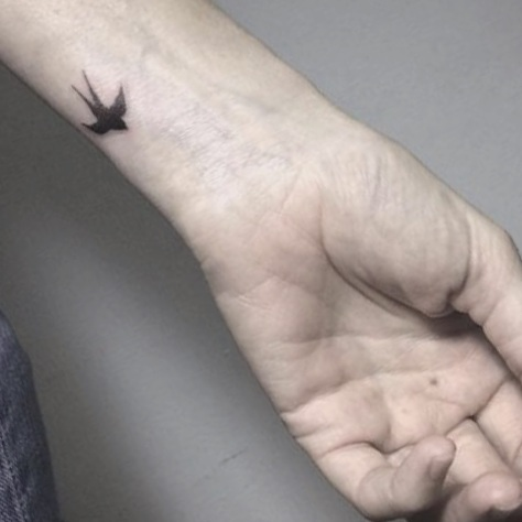 Tattoo de golondrina minimalista en Madriz