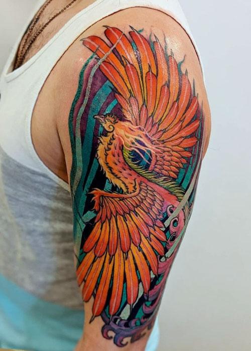 Tatuaje de ave fenix en brazo de hombre en Madrid