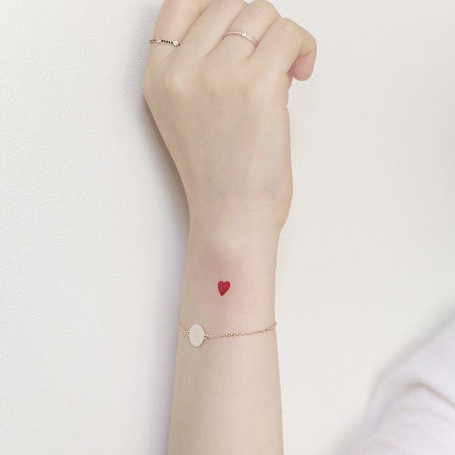 Tatuaje bonito de corazon rojo en la muñeca