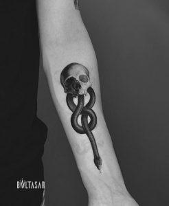 Tatuaje microrealista de calavera con serpiente, realizado en Madrid